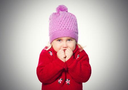 caps: Niña divertida en el casquillo y suéter rojo. Aislado en el fondo gris Foto de archivo