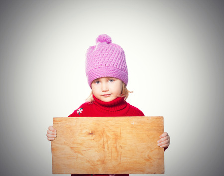 rueful: Little girl holding Board for text. Isolated on gray background