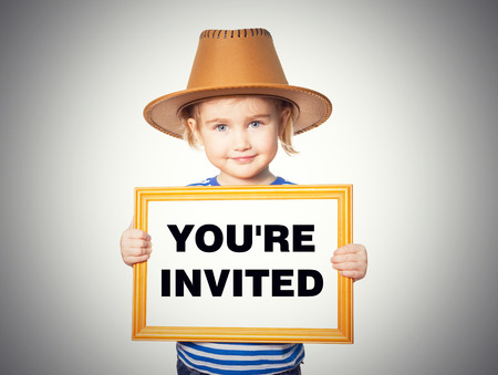 invited: Little Funny girl in striped shirt with blackboard. Text YOURE INVITED. Isolated on gray background. Stock Photo