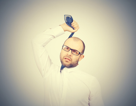 strangling: Suicidal businessman strangling himself tie. Isolated on gray background Stock Photo