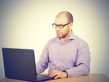 busy beard: Busy man with beard in glasses thinking over laptop with  on the table. Isolated on gray background