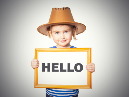 Little Funny girl in striped shirt with blackboard. Text HELLO. Isolated on gray background. Stock Photo