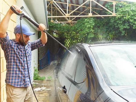 rinse spray hose: Man washing his black car near the house. Stock Photo