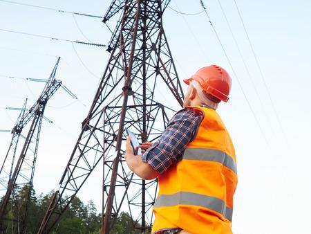 trabajo ingeniero eléctrico. Hablando por teléfono y de trabajo en la tablet.Checking las redes eléctricas. Foto de archivo