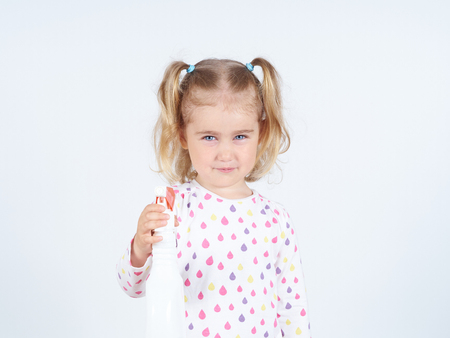 sprayer: Little girl holding a watering spray bottle. sprayer trigger Stock Photo