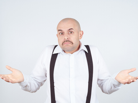 i dont know: bald man shrugging shoulders I dont know gesture Isolated.  Human body language. Stock Photo