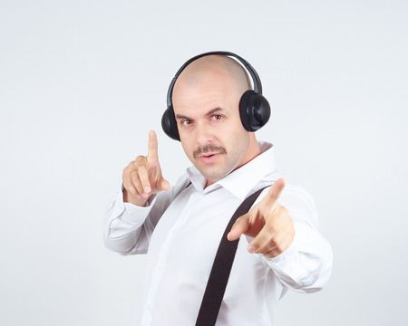 sings: bald man with a mustache businessman listening to music on headphones and sings