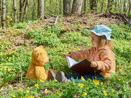 Cute girl reading book Teddy bear on the grass in forest. Flower glade in the forest.