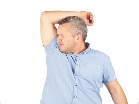 foul: Fat man, smelling sniffing his armpit, something stinks bad, foul odorIsolated on white background. Stock Photo