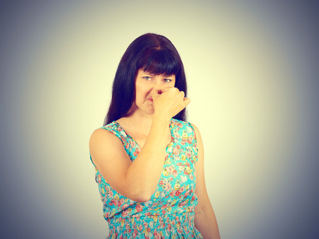 stinks: A young woman pinches the nose with fingers in disgust something stinks. bad smell, isolated. the expression of the human face. language of the body Stock Photo