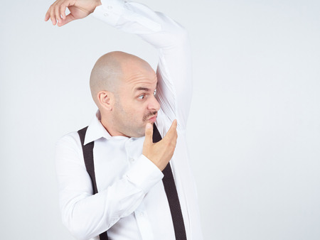 foul: bald man, smelling sniffing his armpit, something stinks bad, foul odor isolated on background.