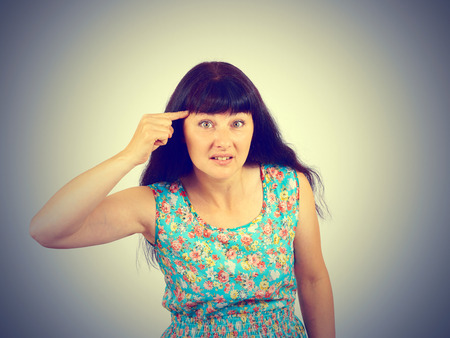 stupid body: Young woman gesturing with her finger against temple, are you crazy. Isolated  Negative emotions facial expression feeling body language Stock Photo