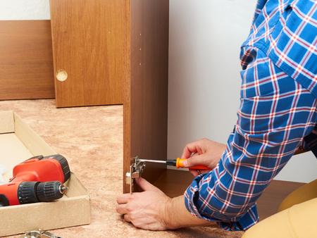 Man in shirt assemble furniture. Domestic work. Craftsman. Carpenter. Stockfoto