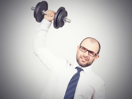 raises: Man Trained businessman raises dumbbell. Isolated on white background