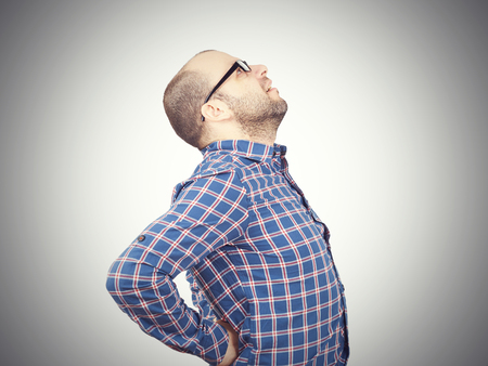throb: Caucasian man in blue shirt struggles with intense back pain on white background.