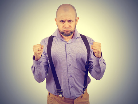 Bald bearded man puffed out his cheeks and clenched his hands into fists. Stock Photo