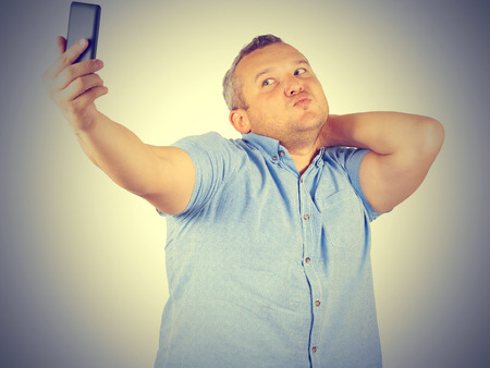 funny picture: Funny picture of  plump man on background. businessman doing selfie. Stock Photo
