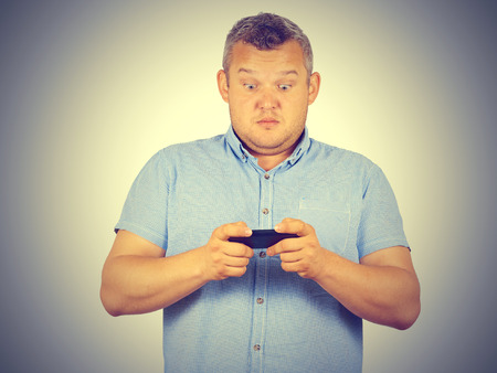 gasping: fat man looks at the phone. Playing on a smartphone. Bad news. Emotions.