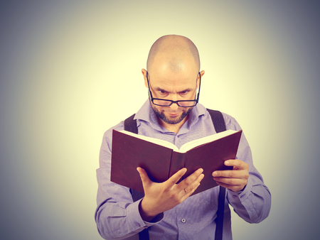 brainy: man caucasian professor in a lavender shirt with a beard reading old book isolated studio on background