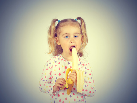 banana: Little girl eating a fresh banana. Healthy eating. Diet. Vegetarianism. Stock Photo