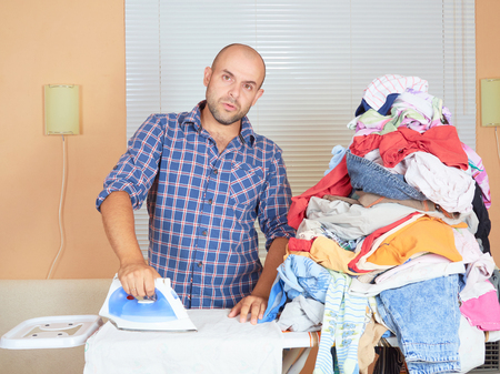 ironed: Caucasian man ironed clothes in the room near the window. Homework.