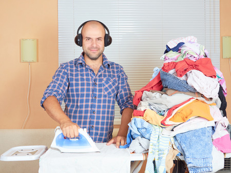 ironed: Caucasian man ironed clothes in the room near the window and listening to music on headphones. Homework.