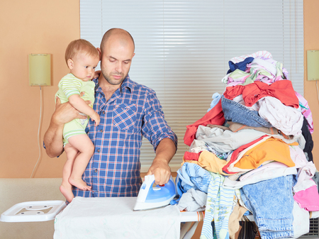 Caucasian man father and son in his hands, ironed clothes in the room near the window. Homework. 写真素材