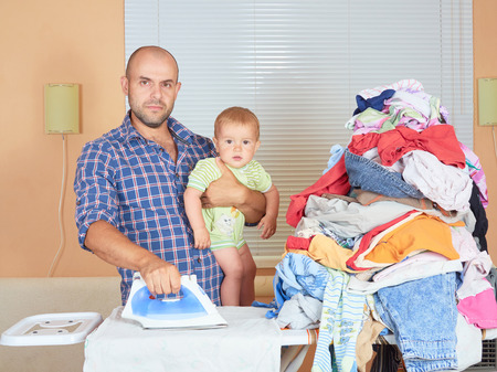 ironed: Caucasian man father and son in his hands, ironed clothes in the room near the window. Homework. Stock Photo