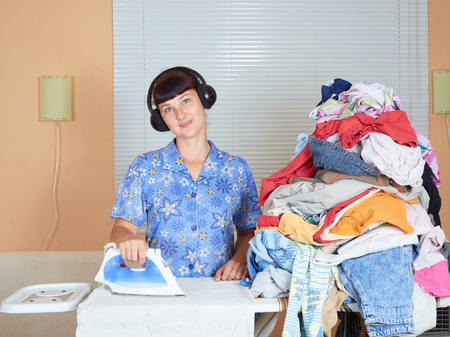 ironed: Young Caucasian woman ironed clothes and listening to music on headphones in the room near the window.