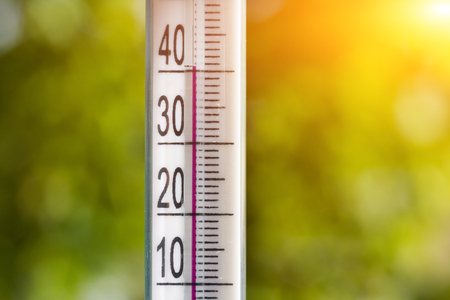 hotter: The thermometer in the heat of summer on a natural background. Stock Photo