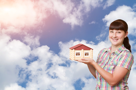 photo real: Young woman holding home isolated on a background of sky and clouds.