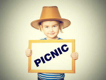 pic nic: Little Funny girl in striped shirt with blackboard. Text PICNIC. Isolated on white background. Stock Photo