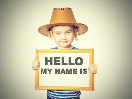 Kleines lustiges Mädchen im gestreiften Hemd mit Tafel. Text HALLO IST MEIN NAME. Isoliert auf weißem Hintergrund. Standard-Bild - 60897310