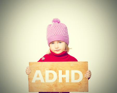 Klein meisje die raad met inscriptie ADHD. Geïsoleerd op witte achtergrond Stockfoto - 60314741