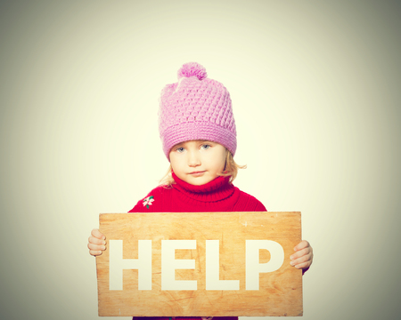 morose: Little girl holding Board with inscription Help. Isolated on white background Stock Photo