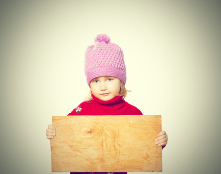 rueful: Little girl holding Board for text. Isolated on white background Stock Photo