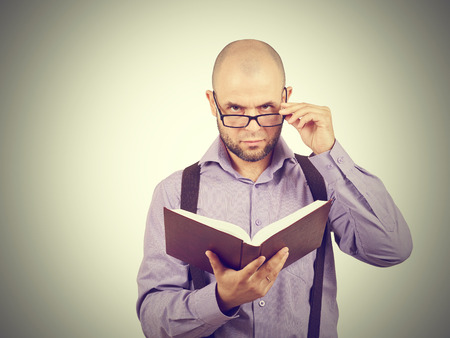 brainy: man caucasian professor in a lavender shirt with a beard reading old book isolated studio  background Stock Photo