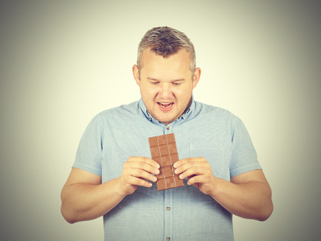 fat man wants to take a bite of chocolate. Diet, overweight, healthy food isolated on background. Stock Photo