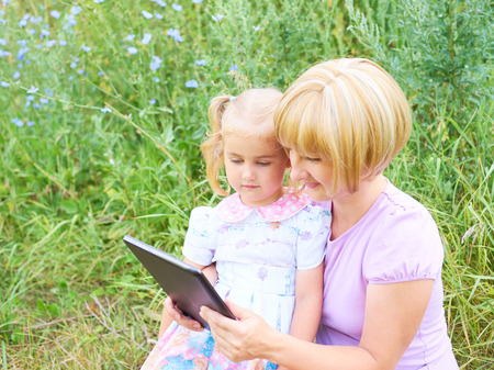 web surfing: Happiness mom and daughter web surfing using tablet outdoors on a sunny day