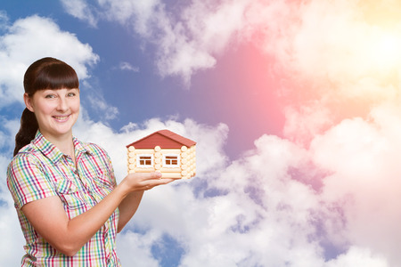 modell: Young woman holding home isolated on a background of sky and clouds.