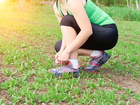 lacing sneakers: Healthy active lifestyle woman athlete tying running shoes. Happy sporty runner girl lacing shoelaces sneakers on summer grass in city park  a fitness morning jog. Stock Photo