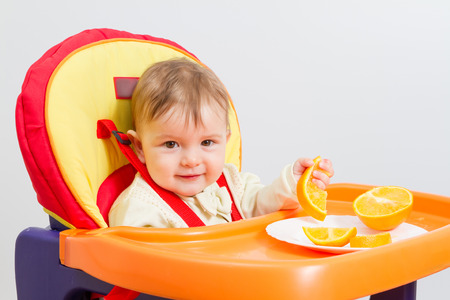 highchair: Baby sitting in highchair and eats an orange.