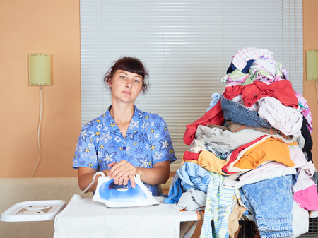 domestic task: Young Caucasian woman ironed clothes in the room near the window.