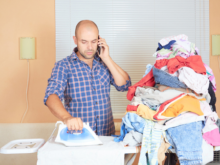 ironed: Caucasian man ironed clothes and talking on the phone. Standing in the room near the window. Homework.
