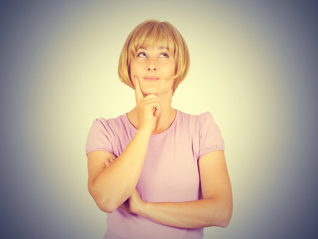 Portrait of a young Thinking  blonde girl. Woman thinks looking up a persons hand. Isolated on background. Stock Photo