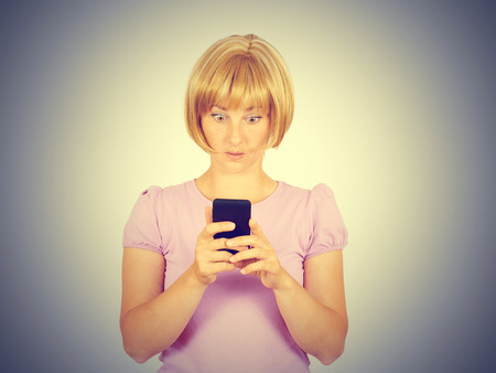 Closeup portrait anxious  young woman looking at phone seeing bad news. Blonde girl in horror reading sms on your smartphone isolated on  background. Stock Photo