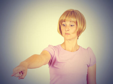 bitchy: Angry young woman pointing finger. isolated on gray wall background.