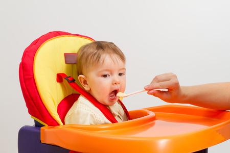 Bebé que come con la cuchara en su casa en silla