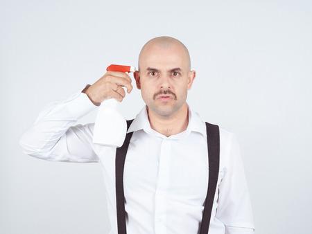 Bald man holding a spray bottle near the temple. Stress.