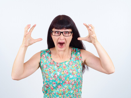 uncontrollable: Young woman in glasses screaming in horror, grimace portrait